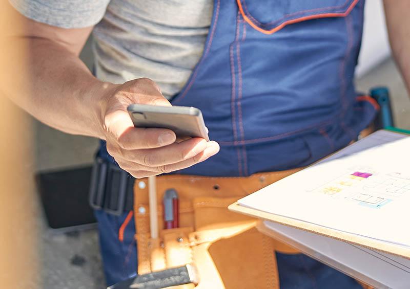 Tradesman user checking mobile for access code