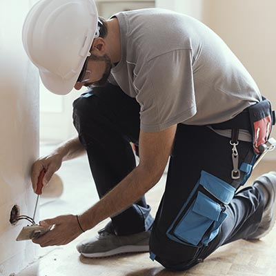 Professional electrician installing sockets using a screwdriver: home renovation and maintenance